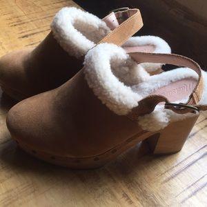 sheeplined clog heels with adjustable straps.